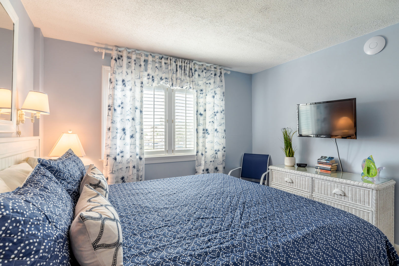 Large TV, dresser, wall-mounted TV, and nightstands of this rental.