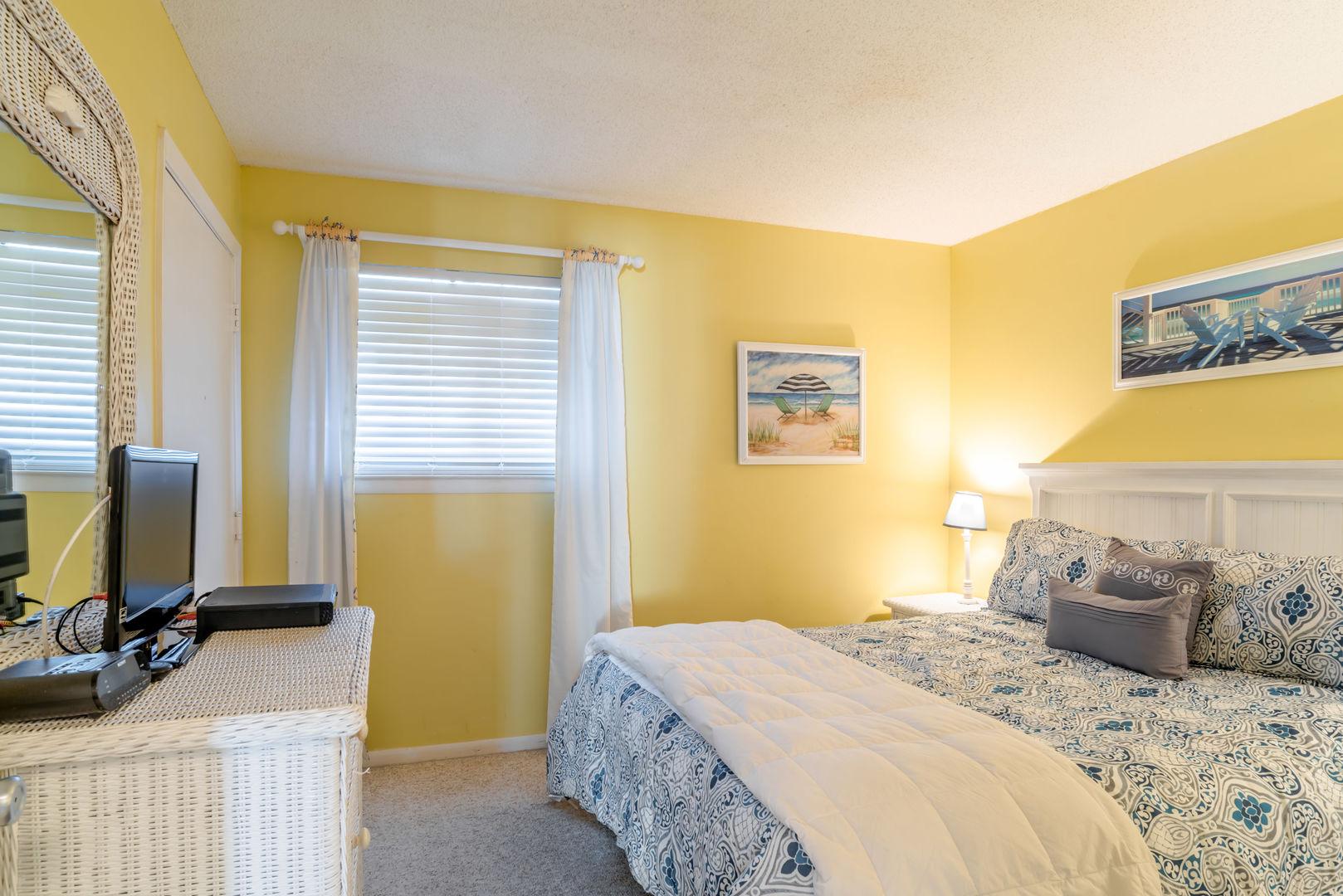 Guest Bedroom With A Queen Bed, nightstands, and vanity.