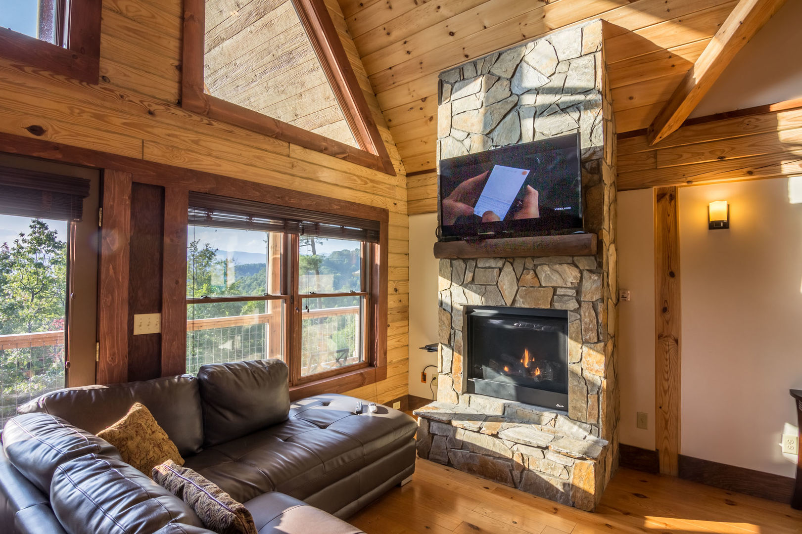 Cozy sectional leather sofa in front of the stone gas log fireplace