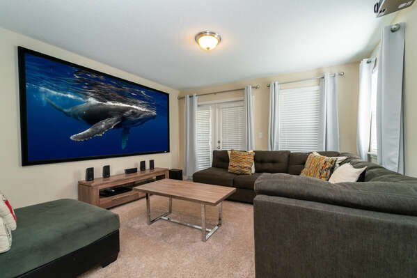 Upstairs movie theatre room with 10ft screen and patio doors to balcony