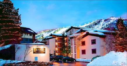 Exterior evening view of the property and night skiing