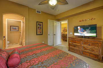 Deluxe king bed, walk-in closet and large TV are features of the primary bedroom.