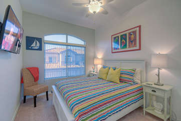 Third bedroom has queen bed, TV and large window with arched transome above for natural light