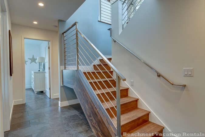 Stairs leading to upstairs living area, master bedroom and second bedroom with queen bed