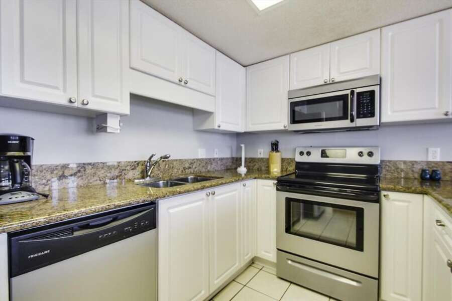 Large Fully Equipped Kitchen with Granite Countertops, Stainless Steel Appliances and Additional Seating at the Breakfast Bar