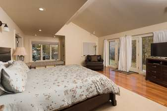Master Bedroom 1 has a King Bed, HDTV, vaulted ceilings and patio