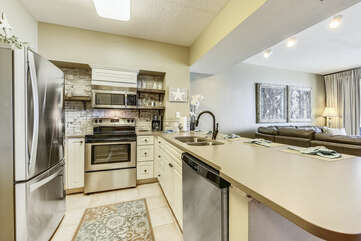Kitchen view, beautiful updated appliances and exposed tiled shelves.