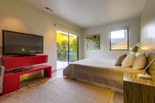 Bedroom with Large Bed, TV Stand, TV, Nightstands, and Sliding Doors.
