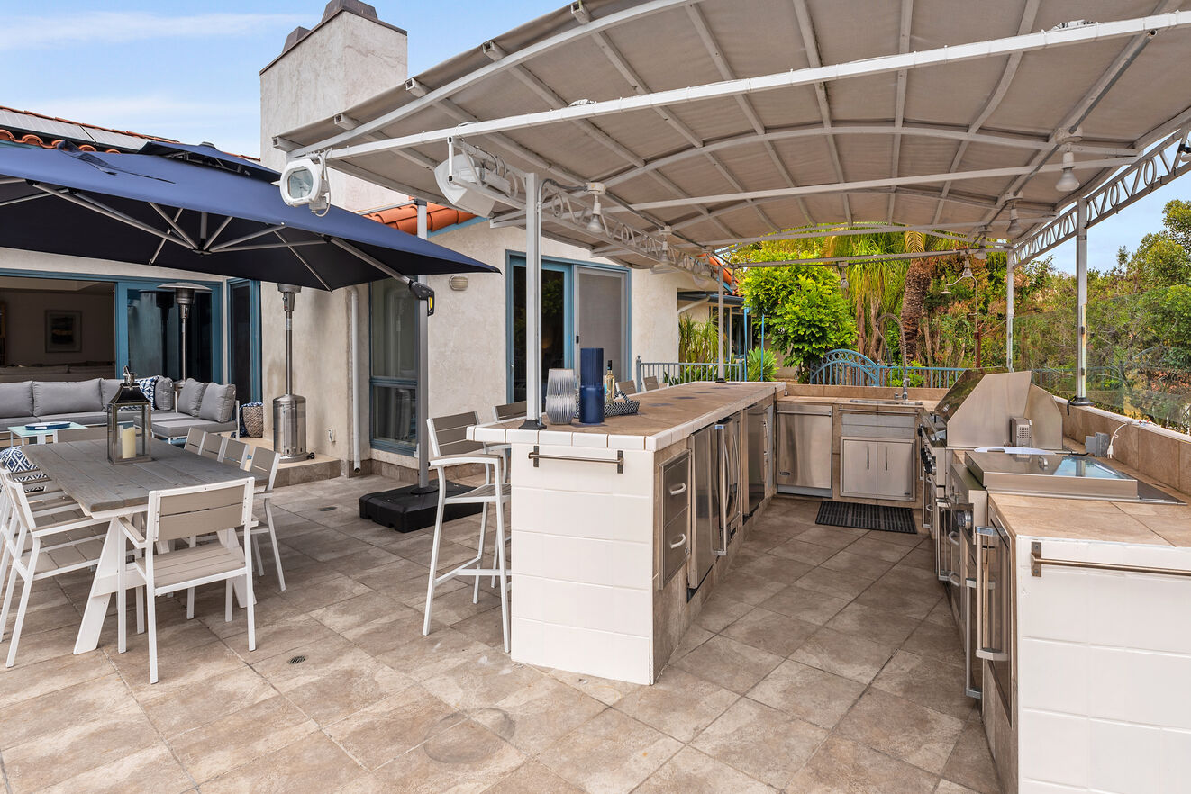A BBQ chef's dream kitchen with outdoor wok, professional grade BBQ, double burners, sink, wine cooler, ice maker, refrigerator and an outdoor shower on the other side.