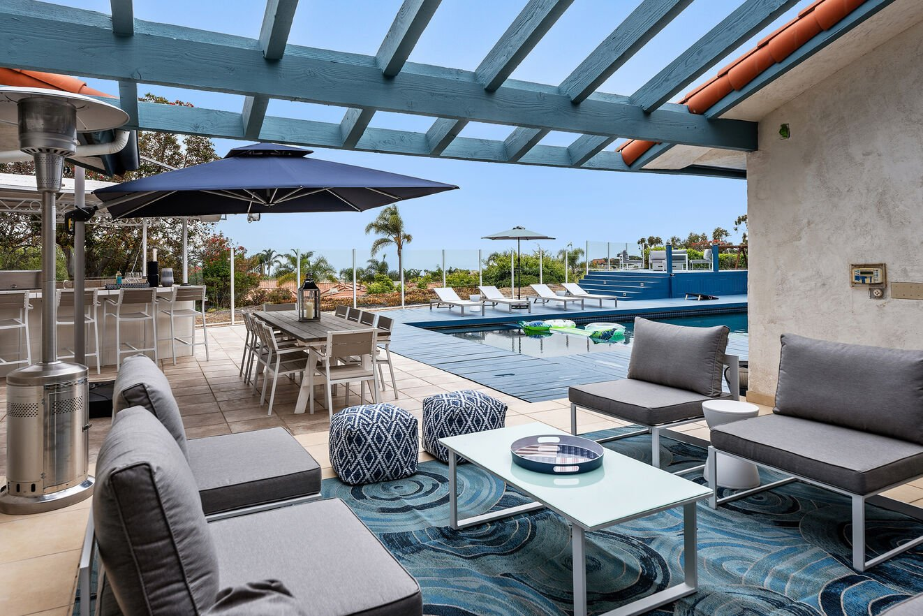 Keep an eye on the outdoor kitchen, dining area and pool from this great outdoor area with a retractable awning.