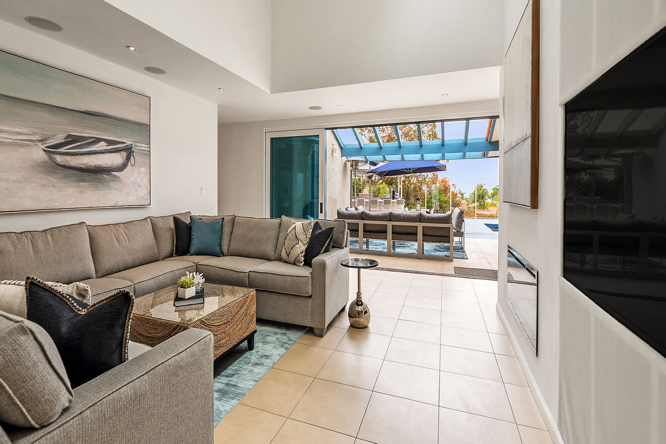 Large central living area with large TV and glass fireplace, wall opens to the outdoor patio areas.