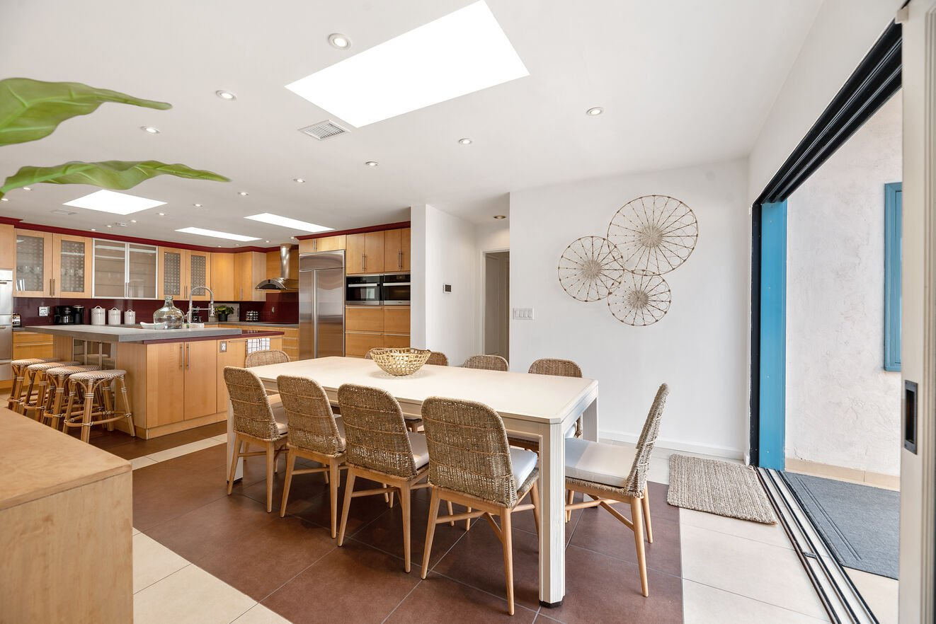 Large open kitchen with bar seating and dining table for 10