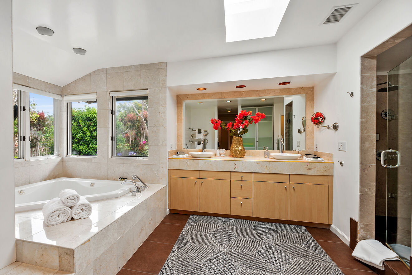 Master bathroom with double vanities, corner jetted tub, shower and closets