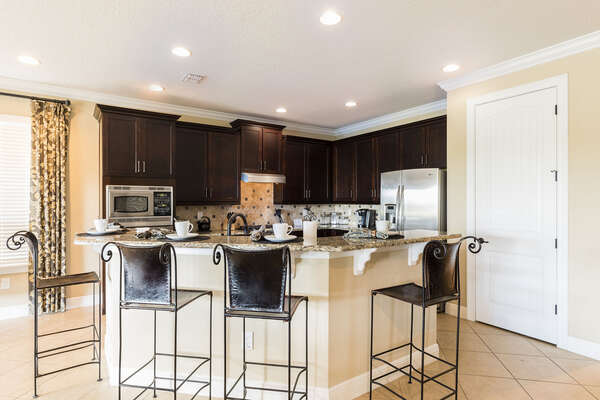 The fully-equipped kitchen features stainless steel appliances and a breakfast bar with seating for 4