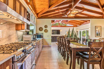 Kitchen with double gas stoves by a dining table with seating for 16.
