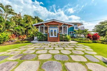 The front yard and exterior of this Kona Hawaii vacation rental, with stone walkway.