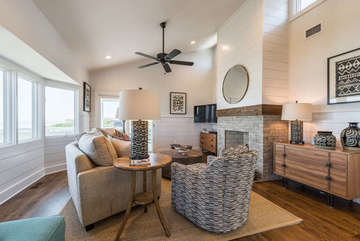 Living area offers plenty of seating, mounted HDTV, walls of windows with ocean view!