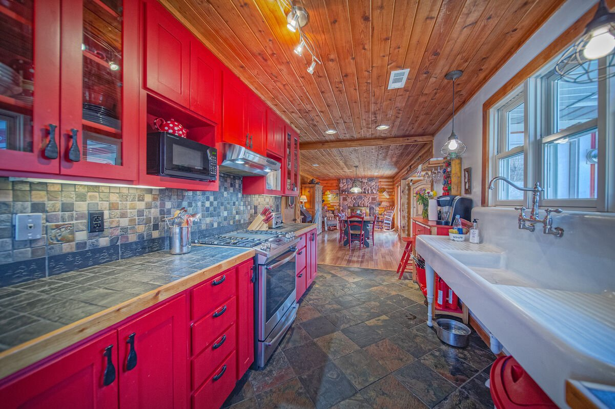 Spacious Kitchen Features Red Cabinets.