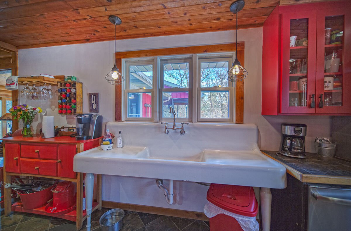Image of Sink and Red Cabinets.