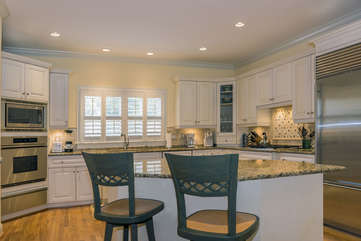 Beautiful upscale kitchen with custom cabinets, granite counter tops and an island with additional seating.