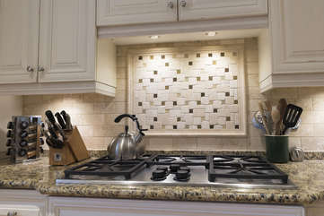 A gourmet gas cook top with counter pop-up ventilation.