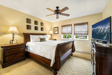 Large bed, twin nightstands, and dresser with flat-screen TV of bedroom 2.