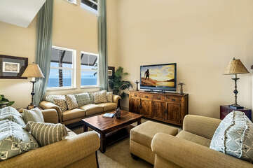 Comfortable seating in the living area, with two couches, armchair, and a flat-screen TV on an entertainment center.