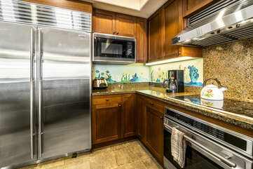 Massive stainless steel fridge, microwave, and oven range in the kitchen of this Kona Hawaii vacation rental.