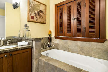 The tub of the master bathroom with a window besides, shutters closed.