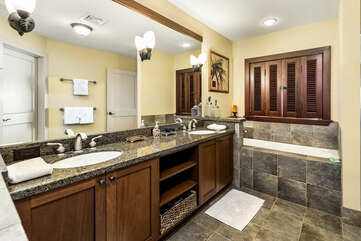 Main ensuite bathroom with his and hers vanity sink and tub.