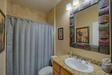 Fourth bathroom features a pretty tiled tub/shower combination and is shared by guests staying in the fifth bedroom.