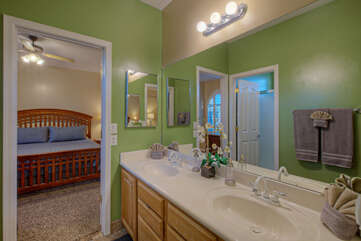 Cheerful Jack and Jill bath with double vanity sinks and walk-in shower is shared between the second and third bedrooms.