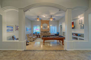 Warm, inviting great room with electric fireplace has stylish and comfy furnishings for viewing Smart TV or cheering for your favorite pool shark.
