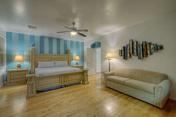 Contemporary primary suite has a king bed, queen sofa, Smart TV and large walk-in closet.