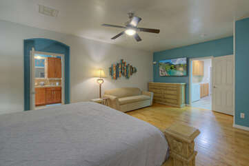 Updated primary suite with king bed has a door to access the back porch for a private and romantic escape to the backyard oasis.
