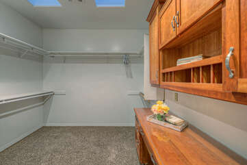 Primary bedroom closet has storage space and built-in desk for completing your remote work in secluded spot.