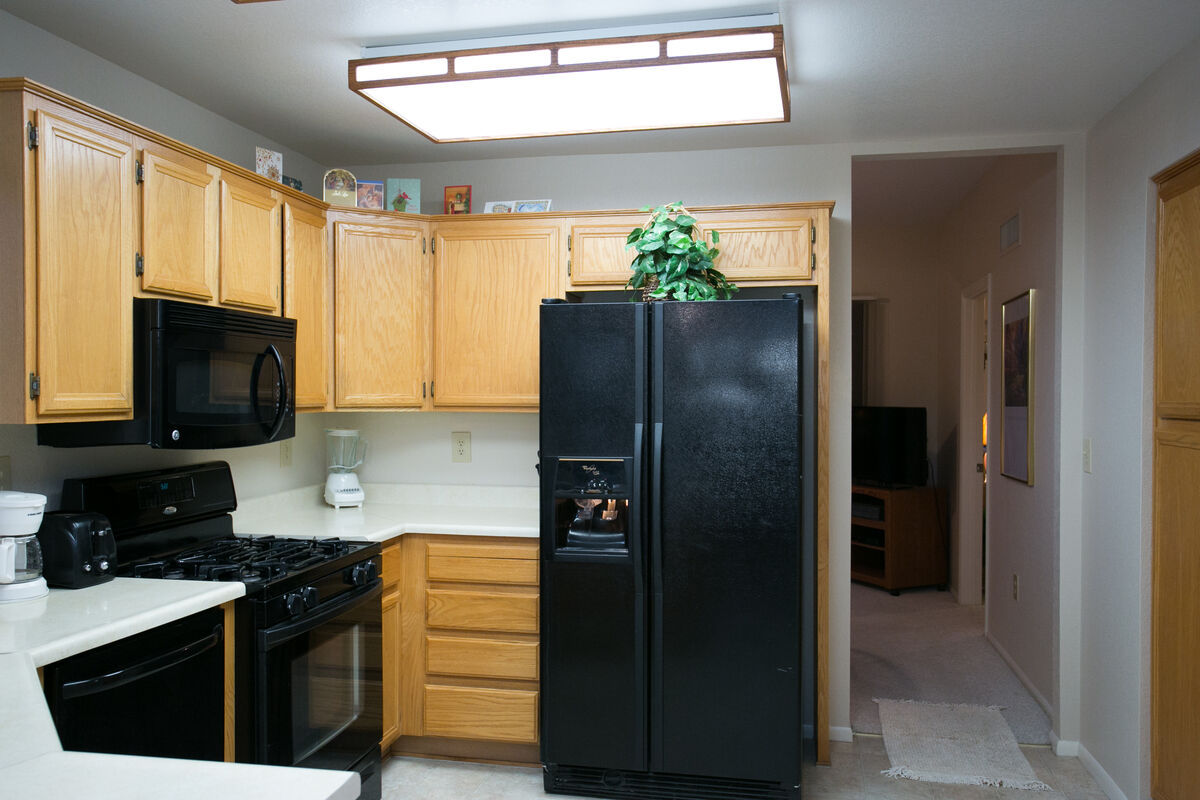 View of the fridge and hallway pass to living area