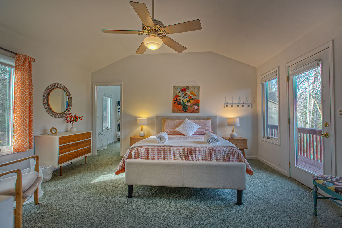 Bedroom with ceiling fan and nearby door to deck