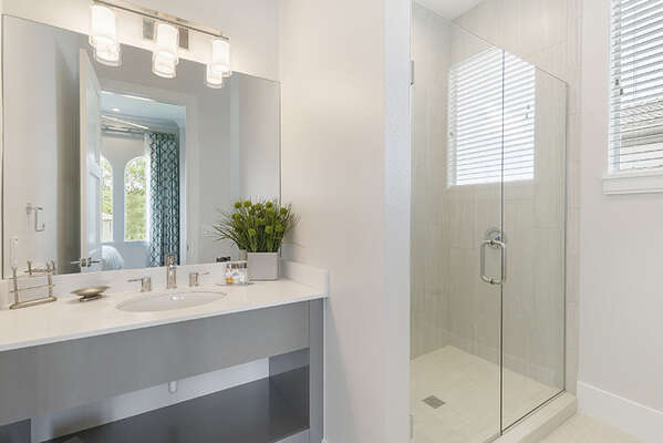 The en-suite bathroom features a glass walk-in shower.