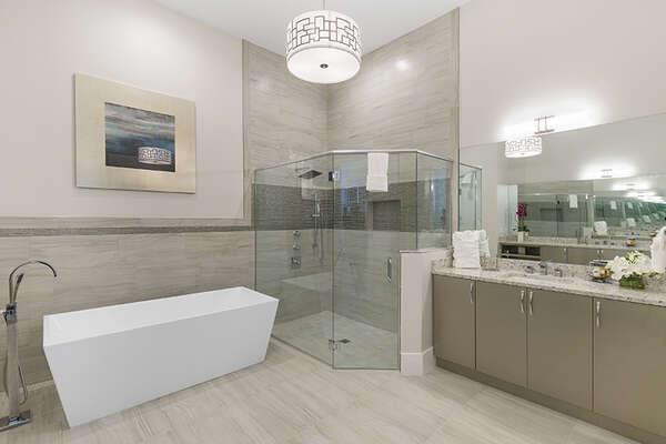 Large en-suite bathroom with glass walk-in shower and garden tub.