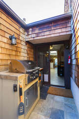 The outdoor patio area has a large 4 burner BBQ grill.