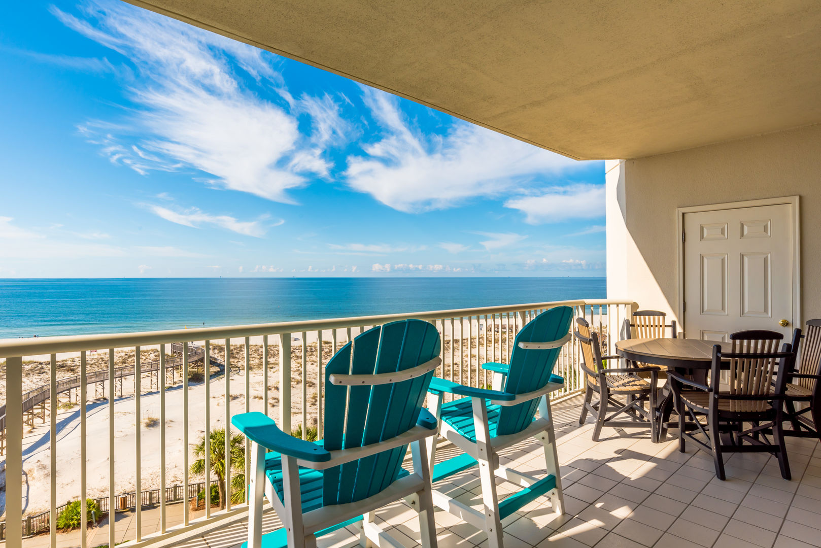 The Balcony with Outdoor Chairs, Table and the Beach View.