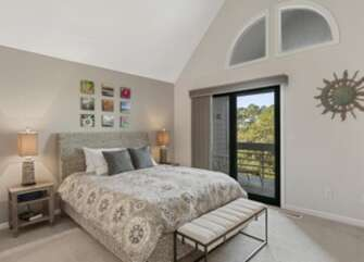 Master bedroom with vaulted ceilings and deck access