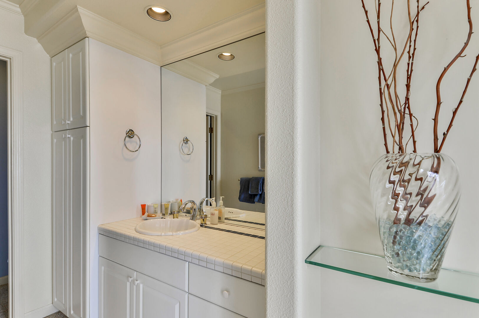 Bathroom Storage Cabinet, Sink, Mirror, Glass Shelf, and a Vase.