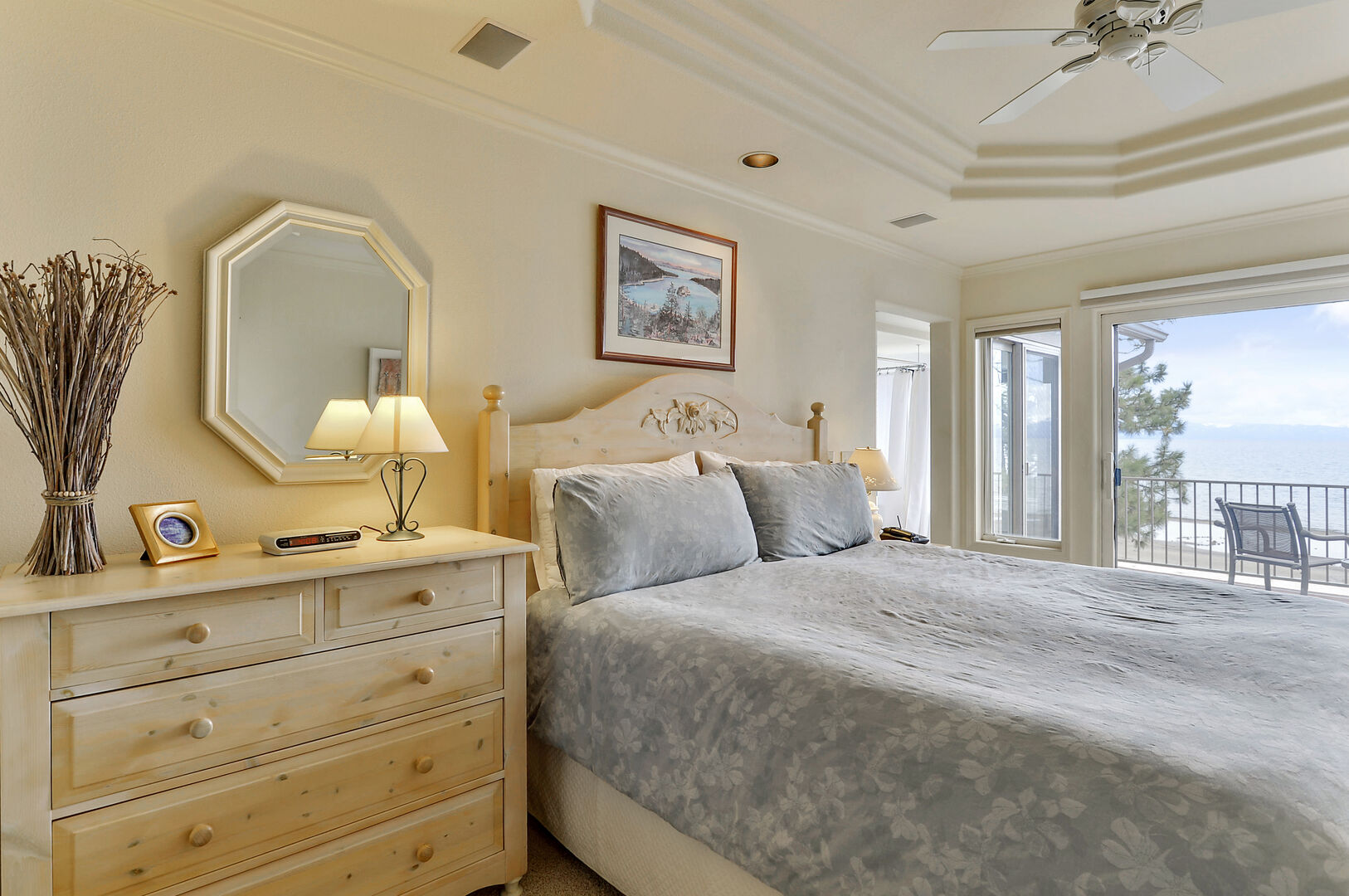 Large Bed, Drawer Dresser, Mirror, Lamp, Window to the Balcony, and Ceiling Fan.