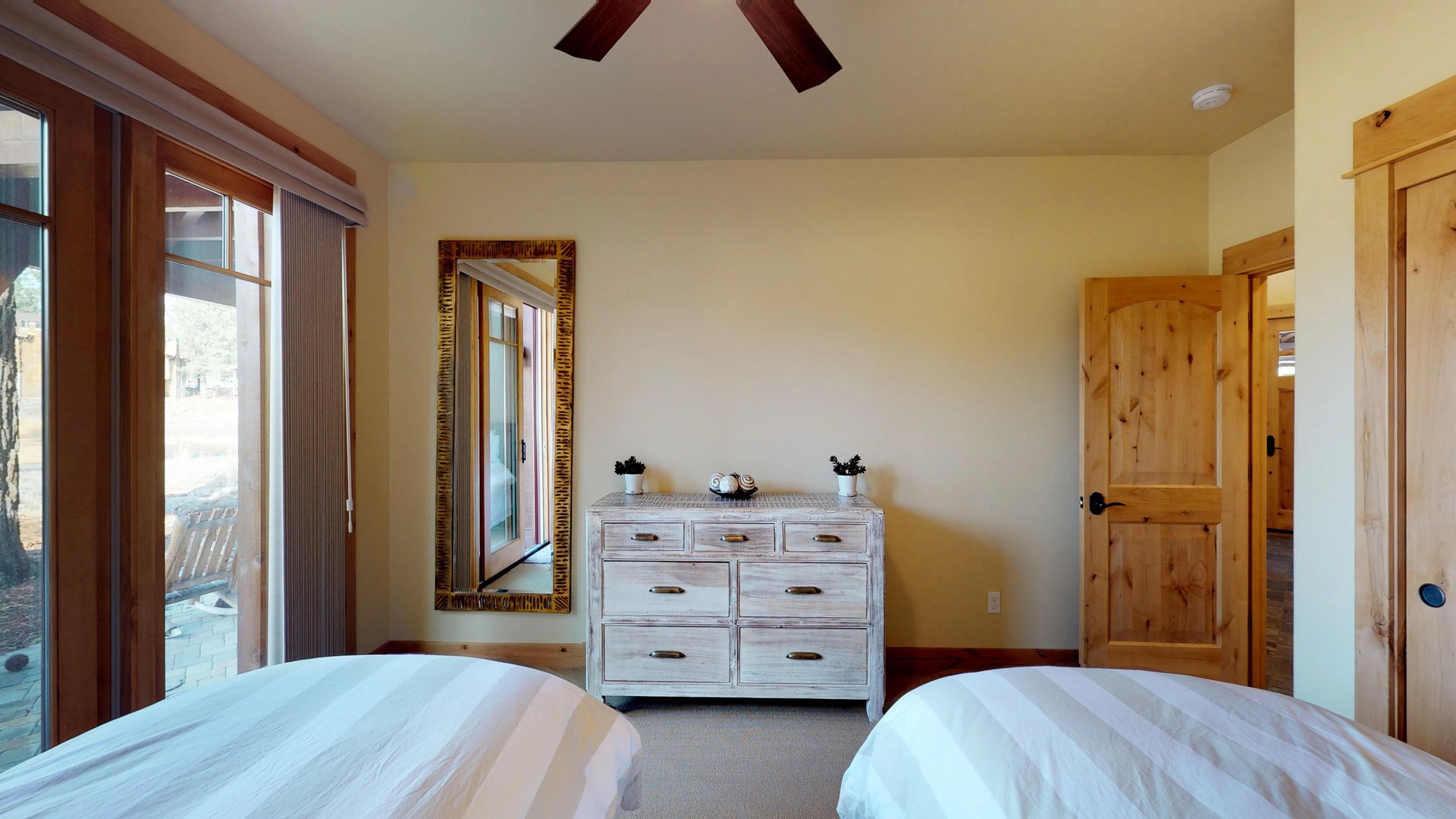 Two Twin-Sized Bed Faces Dresser and Mirror on Wall.