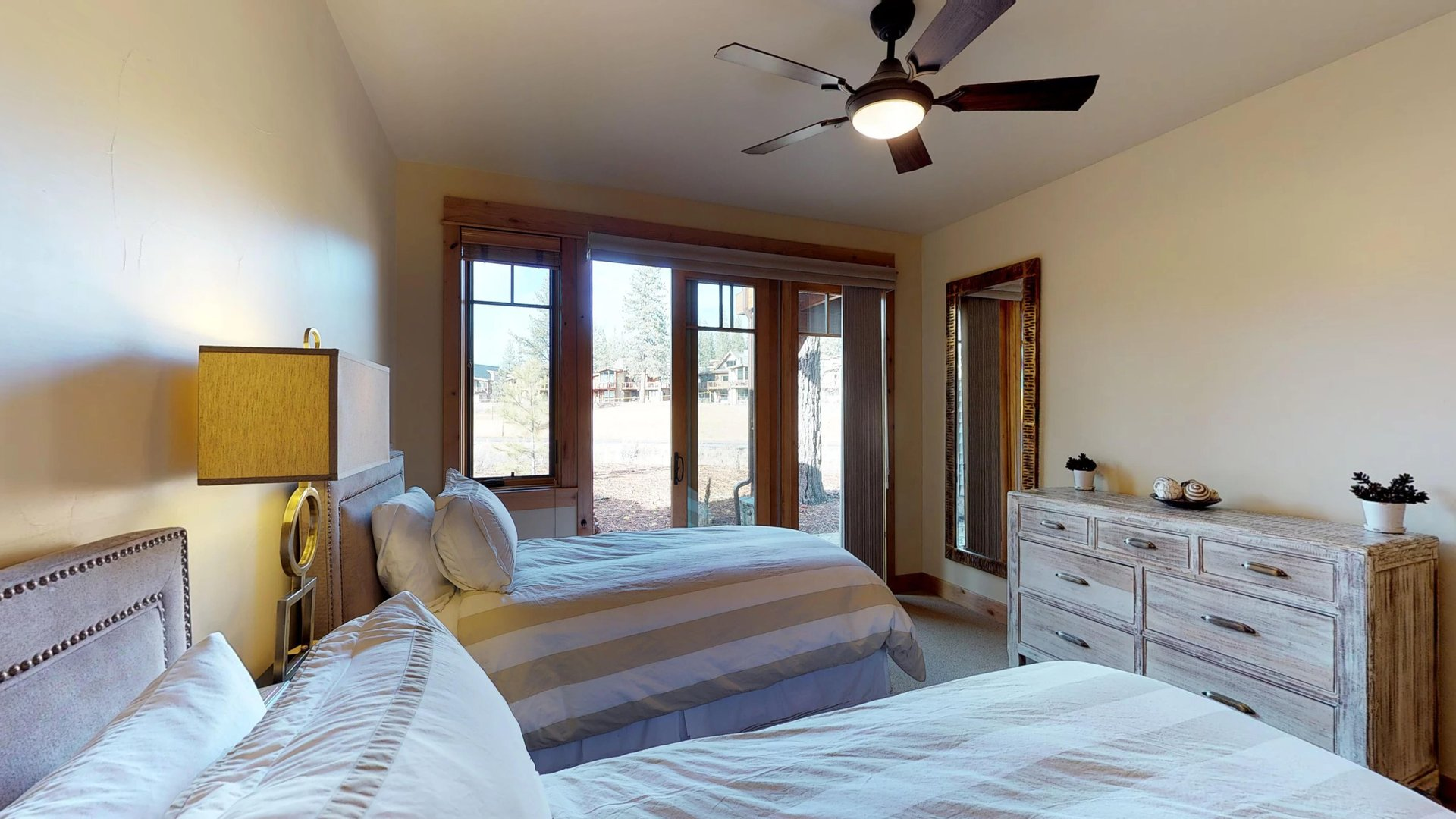 Bedroom Features Two Beds, Wooden Dresser, and Windows.