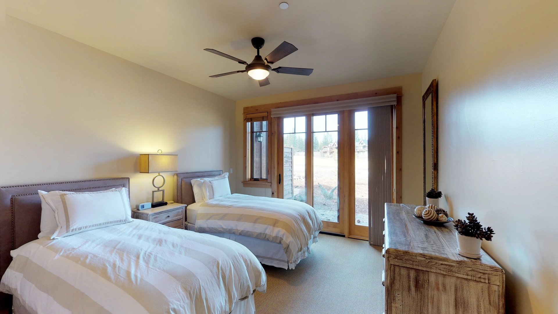 An Image of Two Beds and Dresser in Bedroom.