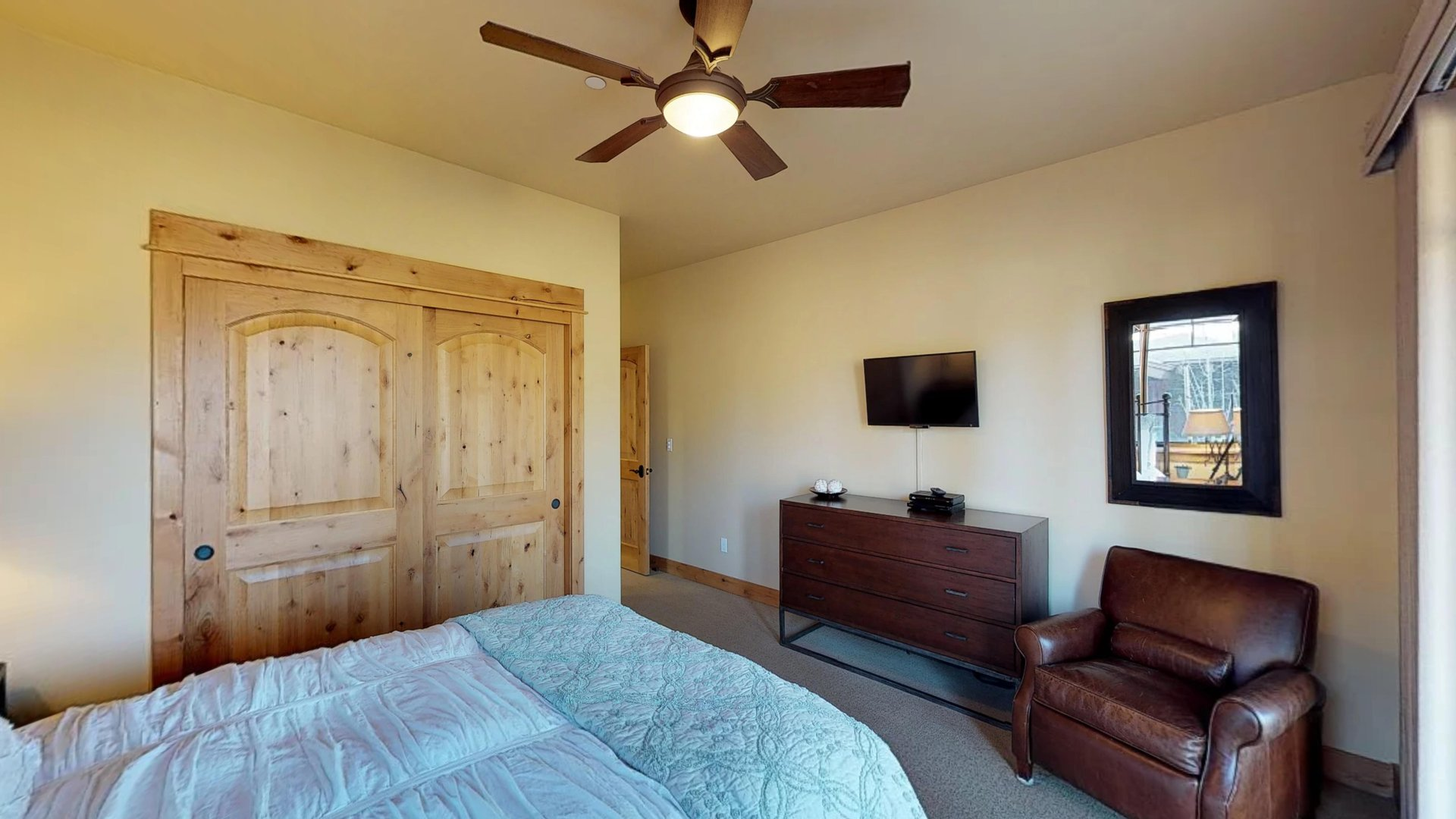 Bedroom Includes Bed, Dresser, Accent Chair, and TV on Wall.