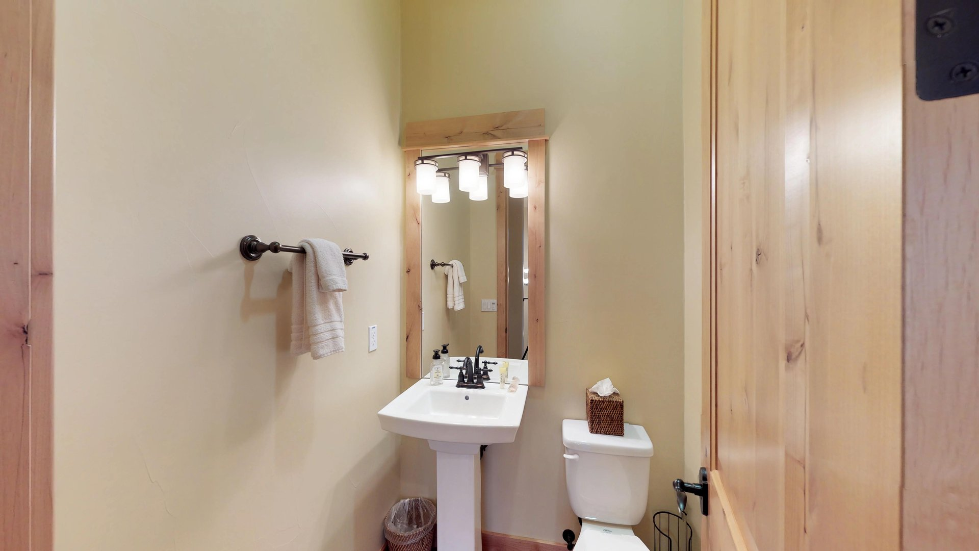 An Image of the Bathroom Sink, Mirror, and Toilet.